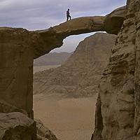 A hiker stands atop a huge rock arch on Jebel [Mount] Burdah, in the Wadi Rum, Jordan. (David Roberts, MR)