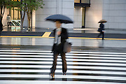 businessperson walking across a zebra crossing during a rainy day