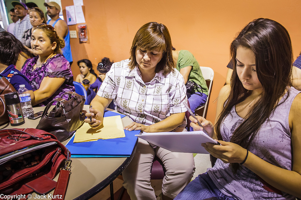 """18 AUGUST 2012 - PHOENIX, AZ:  Woman go over a list of the paperwork needed to participate in the """"deferred action"""" program during a deferred action workshop in Phoenix. More than 1000 people attended a series of 90 minute workshops in Phoenix Saturday on the """"deferred action"""" announced by President Obama in June. Under the plan, young people brought to the US without papers, would under certain circumstances, not be subject to deportation. The plan mirrors some aspects the DREAM Act (acronym for Development, Relief, and Education for Alien Minors), that immigration advocates have sought for years. The workshops were sponsored by No DREAM Deferred Coalition.  PHOTO BY JACK KURTZ"""