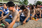 """15 MARCH 2014 - NAKHON CHAI SI, NAKHON PATHOM, THAILAND: Men covered in tattoos pray at the Wat Bang Phra tattoo festival. Wat Bang Phra is the best known """"Sak Yant"""" tattoo temple in Thailand. It's located in Nakhon Pathom province, about 40 miles from Bangkok. The tattoos are given with hollow stainless steel needles and are thought to possess magical powers of protection. The tattoos, which are given by Buddhist monks, are popular with soldiers, policeman and gangsters, people who generally live in harm's way. The tattoo must be activated to remain powerful and the annual Wai Khru Ceremony (tattoo festival) at the temple draws thousands of devotees who come to the temple to activate or renew the tattoos. People go into trance like states and then assume the personality of their tattoo, so people with tiger tattoos assume the personality of a tiger, people with monkey tattoos take on the personality of a monkey and so on. In recent years the tattoo festival has become popular with tourists who make the trip to Nakorn Pathom province to see a side of """"exotic"""" Thailand.   PHOTO BY JACK KURTZ"""
