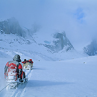 BAFFIN ISLAND, Nunavut, Canada. Inuit snowmobiles pull mountaineering expedition members across frozen lake in remote Stewart Valley, north of Clyde River.  The temperature is below zero, F, and Sail Peaks are in background.