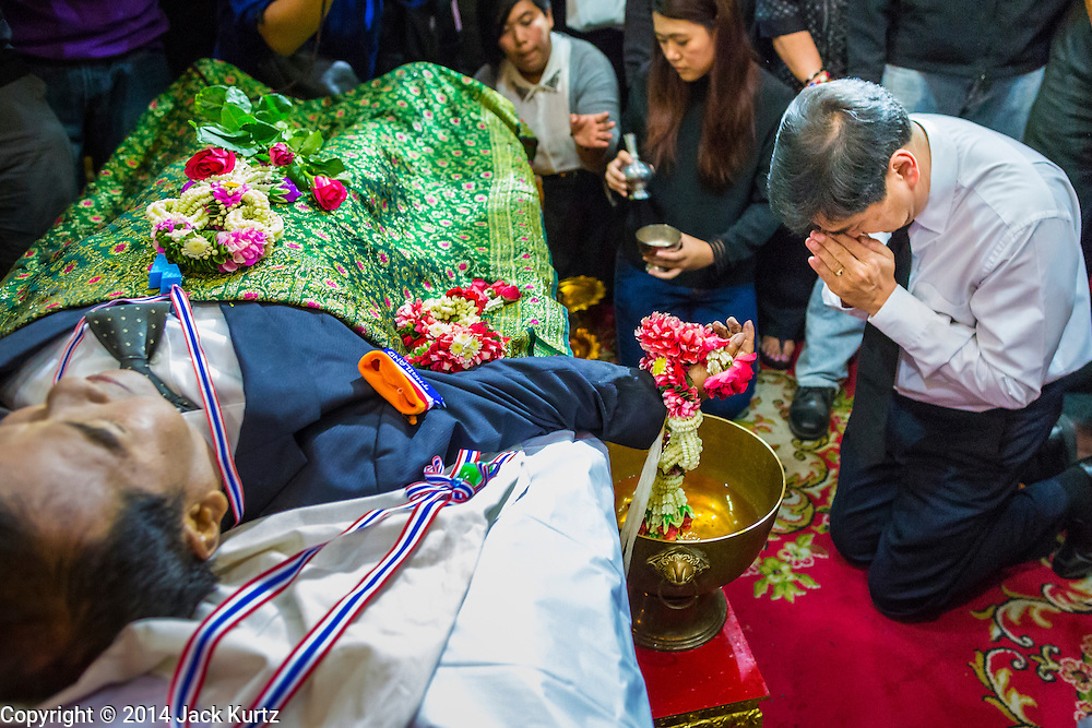27 JANUARY 2014 - BANGKOK, THAILAND: ABHISIT VEJJAJIVA, former Prime Minister of Thailand and a leader of the anti-government movement, prays after  washing the hand of his friend and colleague Suthin Taratin during bathing rites for murdered anti-government leader at Wat Sommanat Rajavaravihara in Bangkok. In Thai tradition, after death a bathing ceremony takes place in which relatives and friends pour water over one hand of the deceased. Suthin was a core leader of the People's Democratic Force to Overthrow Thaksinism (Pefot), one of several organizations leading protests against the elected government of Thai Prime Minister Yingluck Shinawatra. He was murdered Sunday, Jan. 28, while he was leading a rally to prevent voters from reaching a polling center in the Bang Na district of Bangkok.     PHOTO BY JACK KURTZ