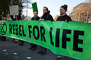 Climate change activists from the Extinction Rebellion group block roads in central London at Tower Hill in protest that the government is not doing enough to avoid catastrophic climate change and to demand the government take radical action to save the planet, on 21st November 2018 in London, England, United Kingdom. Extinction Rebellion is a climate change group started in 2018 and has gained a huge following of people committed to peaceful protests.