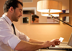 Businessman holding a credit card and typing on a keyboard