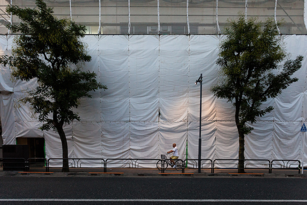 A Japanese man rides his bicycle by the scaffolding on a construction site in Koenji, Tokyo, Japan. Sunday October 2nd 2016