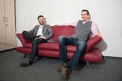 Two young men relaxing on office sofa waiting