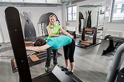 Fitness room mature woman stretching trainer