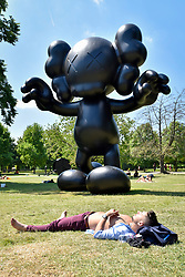 """© Licensed to London News Pictures. 05/07/2017. London, UK. """"Final Days"""", 2013, by KAWS.  The Frieze Sculpture festival opens to the public in Regent's Park.  Featuring outdoor works by leading artists from around the world the sculptures are on display from 5 July to 8 October 2017.  Photo credit : Stephen Chung/LNP"""