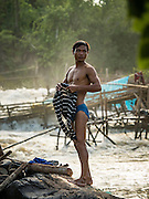 18 JUNE 2016 - DON KHONE, CHAMPASAK, LAOS: A fisherman changes back into his street clothes after working his traps at  Khon Pa Soi Waterfalls, on the east side of Don Khon. It's the smaller of the two waterfalls in Don Khon. Fishermen have constructed an elaborate system of rope bridges over the falls they use to get to the fish traps they set. Fishermen in the area are contending with lower yields and smaller fish, threatening their way of life. The Mekong River is one of the most biodiverse and productive rivers on Earth. It is a global hotspot for freshwater fishes: over 1,000 species have been recorded there, second only to the Amazon. The Mekong River is also the most productive inland fishery in the world. The total harvest of fish from the Mekong is approximately 2.5 million metric tons per year. By some estimates the harvest in the Tonle Sap (in Cambodia) had doubled from 1940 to 1995, but the number of people fishing the in the lake has quadrupled, so the harvest per person is cut in half. There is evidence of over fishing in the Mekong - populations of large fish have shrunk and fishermen are bringing in smaller and smaller fish.        PHOTO BY JACK KURTZ
