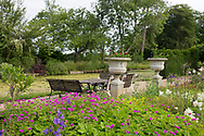 Stone urns and a seating area surrounded by pink Geraniums and Astilbe in the formal garden next to the moat in the garden at Hindringham Hall, Hindringham, Norfolk, UK