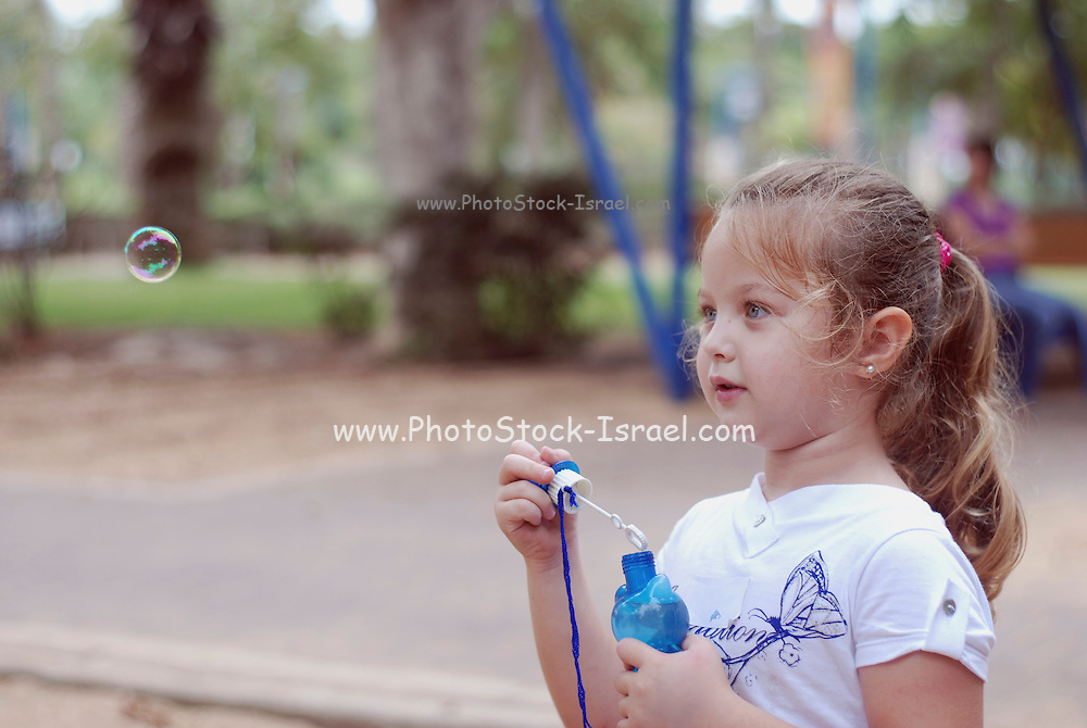 Girl of 5 blowing soap bubbles
