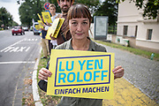 Independent candidate for the federal elections from Potsdam Lu Yen Roloff, demonstrates as party leader and Chancellor candidate of the Christian Democratic Union of Germany  (CDU), Armin Laschet attends an election campaign event near the Glienicker Brücke in Potsdam, Brandenburg, Germany August 13, 2021. Germany will hold its federal elections on September 26, 2021.