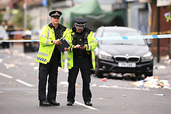 Police officers assess the scene in Claremont Road, Moss Side, Manchester, where several people have been injured after a shooting.