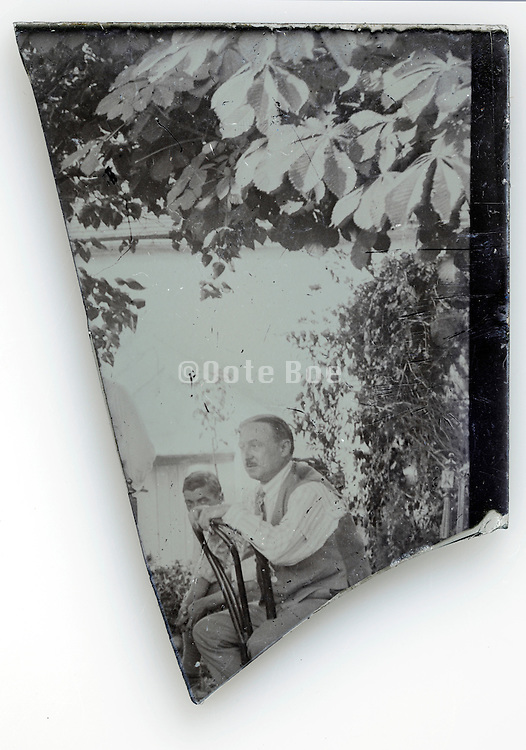part of glass plate image with man sitting on a chair in garden