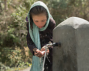 Girls drinking water. Water pipe project initiated by the Aga Khan Foundation .  The traditional life of the Wakhi people, in the Wakhan corridor, amongst the Pamir mountains.