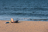 A photo of lounge chairs on an empty Spring Lake beach taken in the soft light of an early morning sun.