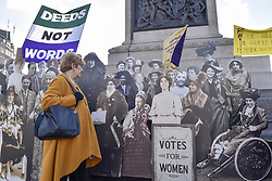 """February 6, 2018 - London, UK - LONDON, UK.  Angela Stern from London poses against a pop-up exhibition featuring 59 life-sized images of campaigners, along with famous rallying slogans such as """"deeds not words"""" in Trafalgar Square marking 100 years since the Representation of the People Act was passed, granting some women over the 30 in the UK the right to vote for the first time. (Credit Image: © Stephen Chung/London News Pictures via ZUMA Wire)"""