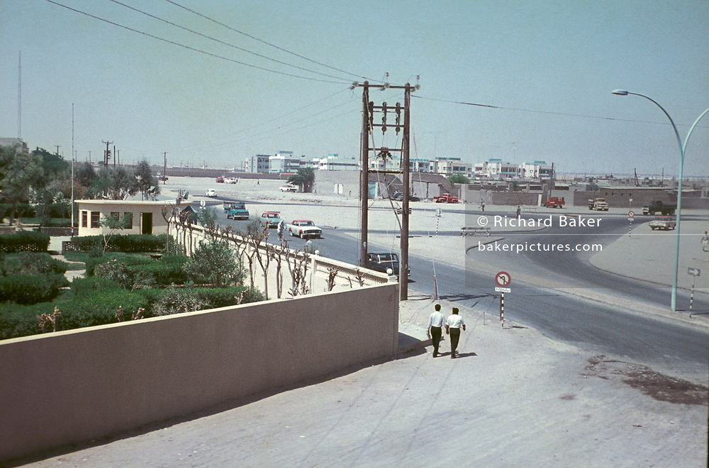 "Two men walk around the corner of a property wall and towards a roundabout, on 20th March 1968, in Kuwait, Persian Gulf. The period of 1946-82 is often termed ""the golden period of Kuwait"" by western academics. In the 1960s and 1970s, Kuwait was considered by some as the most developed country in the region. Kuwait was the pioneer in the Middle East in diversifying its earnings away from oil exports. The Kuwait Investment Authority is the world's first sovereign wealth fund. From the 1970s onward, Kuwait scored highest of all Arab countries on the Human Development Index."
