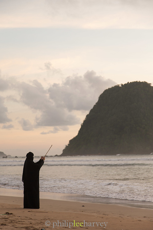 Woman wearing Niqab stood beside the sea holding a stick in the air,  Red Island Beach, Red Island, Banyuwangi Regency, East Java, Indonesia, Southeast Asia