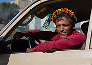 """FLOWER POWER IN SAUDI ARABIA<br /> """"You have 15 minutes to take pictures, then we gotta leave. Those people are crazy! Do it quickly please!"""" My police escort was nervous, because visiting the Flower Men in the deep south of Saudi Arabia was a real headache. And obviously, they know the situation better than anyone, as they were part of the Qahtani tribe living in the Jizan and Asir southern provinces. This scene happened during my trip ten years ago.<br /> <br /> No tourists were allowed ever since until December, 2018. The closed kingdom finally cracked the door open for tourists again, only for a few weeks though, thanks to Supercoppa Italiana Juventus Vs Milan in Jeddah. Such a rare opportunity to visit Flower Men another time, and see how they deal with the war against their cousins in Yemen as well as the shy opening of the Kingdom.<br /> <br /> You know for sure when you arrive in the area of the Flower Men, because you will notice the incredible watchtowers and houses built like small castles. On one hand, these defensive architectural elements indicate that the locals are living in the fear of constant attacks for centuries. On the other hand, this also has given them a very sturdy character and a fierce spirit of independence.<br /> Interestingly, those tough fighters also come with tender hearts in this peninsula, as they all desire to look attractive. You won't see them wearing the traditional keffieh, instead, the descendants of the ancient legendary Tihama and Asir tribes love to wear colorful garlands in their daily life.<br /> The first to have studied this tribe was the late french researcher Thierry Mauger. In the 80's , he traveled around the area and took pictures to make a book. He got into a lot of troubles and was even nearly raped by male villagers! <br /> I believed it was a smart idea to bring back his old photo book in the villages. However, it was not. As soon as I opened it in front of the Flower Men, they were shocked to see their women"""