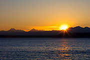 The sun sets behind the Olympic Mountains in this view from across Puget Sound in Edmonds, Washington.