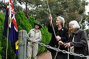 Nell O'Grady (centre) and Jan Yurisich (right) raise the Western Australian State flag.