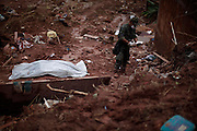 A man checks a notebook found near the body of Samara Coelho da Silva, 13, after removing her from an area afected by a landslide at Prainha neighborhood in Nova Friburgo, Brazil, Monday, Jan. 17, 2011. <br /> <br /> A series of flash floods and mudslides struck several cities in Rio de Janeiro State, destroying houses, roads and more. More than 900 people are reported to have been killed and over 300 remain missing in this, Brazil's worst-ever natural disaster.