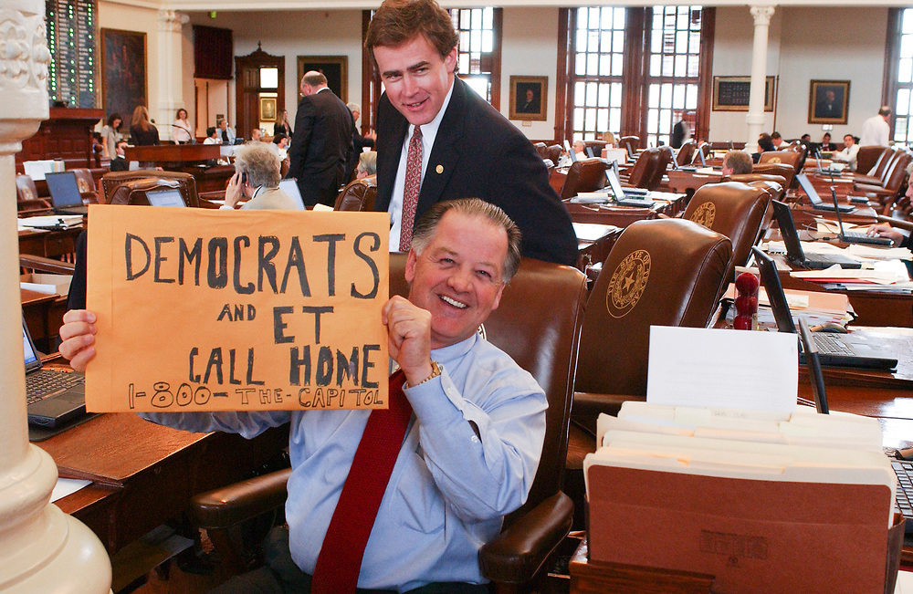 Images from 2003's Democratic walkout in the Texas House from May 12-13, 2003 during the 78th session of the Texas Legislature include Rep. Tommy Merritt, R-Longview holding a sign while Rep. Dan Branch, R-Dallas watches.