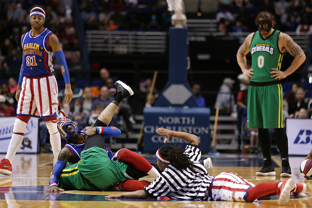 Globetrotters' guard Firefly (3) takes down a Washington Generals player during the second half of the game in Charleston. <br /> The Harlem Globetrotters World Tour in Charleston, S.C. on Saturday, March 24, 2018.<br /> Zach Bland Photo
