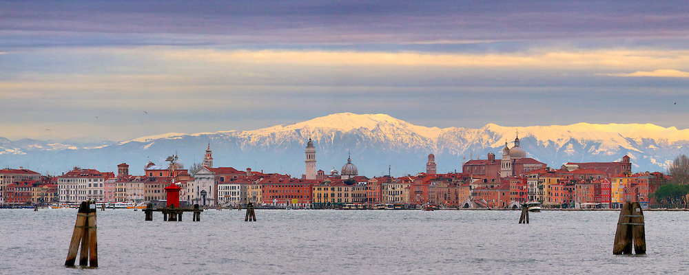 An unusual view of the Venice skyline with the snow-covered Alps in the background. Taken from the Lido about 30 minutes after sunrise on a cold and windy morning at the beginning of December.