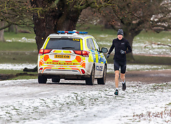 © Licensed to London News Pictures. 26/01/2021. London, UK. Police patrol Richmond Park in South West London as a runner enjoys the remains of the melting snow as the government mulls over plans to force all UK arrivals at airports and ports to quarantine in hotels across the country as the coronavirus crisis continues into 2021. Photo credit: Alex Lentati/LNP