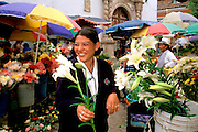 ECUADOR, HIGHLANDS, CUENCA students in main flower market