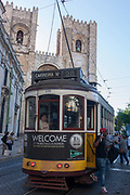 Stopped beneath the Se cathedral, a number 28 tram passenger descends on to the cobbled street, on 13th July 2016, in Lisbon, Portugal. The 28 is one of the trams not only used by the people of the capital but also of an increasing number of tourists who ride the entire route from Prazeres cemetery in the west of the city, to Rossio in the centre, after a loop through some of the most amazing streets and landmarks. So crowded is the 28, that older locals often cant sit down, having to stand over younger, inconsiderate tourist families who want a window seat for the entire journey - and back. Notices at termini remind visitors that this is a public service and to consider locals.