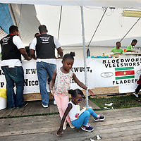 Nederland, Amsterdam , 27 juli 2014.<br /> het Kwaku-festival, in het Bijlmerpark in Amsterdam-Zuidoost.<br /> Dat festival is jarenlang het toneel geweest van gedoe, met betrokkenen binnen de organisatie die elkaar de tent uitvochten en zo. Maar sinds vorig jaar , sinds er een nieuwe organisatie achter zit, loopt het goed.<br /> één stand, die van Wan2Connect, een netwerk van etnisch ondernemers dat beginnende allochtonen ondernemers op weg wil helpen. De gedachte is dat beginnende allochtone ondernemers veel vaker failliet gaan dan autochtone, omdat ze bepaalde vaardigheden missen. Dit netwerk wil hen daarbij helpen, en wil op Kwaku zichzelf presenteren, onder meer door bezoekers een soort 'ondernemerstest' af te nemen.<br /> Op de foto: 2 vertegenwoordigers van de Wan2connect stand in gesprek met allochtone ondernemers van een sparerib stand.<br /> Foto:Jean-Pierre Jans