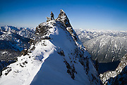 Climber Kevin Steffa stands proudly on a narrow ridge during a winter ascent of Snoqualmie Mountain, Snoqualmie Pass, Washington.