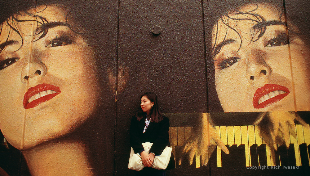 Young woman stands against wall of Parco store, Shibuya district, Tokyo, Japan