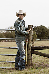 rugged cowboy working on a fence on a ranch