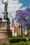 Statue of Independence leader Miguel Hidalgo and the Parroquia Nuestra Señora de Dolores Catholic Church in the Plaza Principal with flowering Jacaranda behind in Dolores Hidalgo, Guanajuato, Mexico. Hildago was a parish priest who issued the now world famous Grito - a call to arms for Mexican independence from Spain.