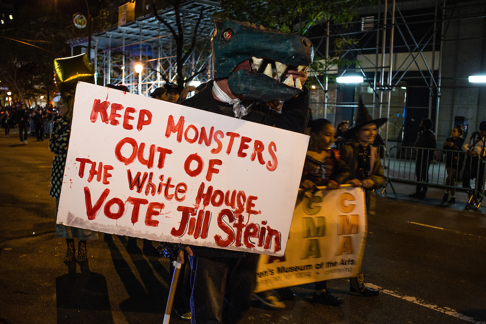 """New York, NY - 31 October 2016. A man in a monster costume carries a sign that reads """"Keep monsters out of the White House vote Jill Stein"""" in the annual Greenwich Village Halloween parade. Stein is running as a Green Party candidate."""