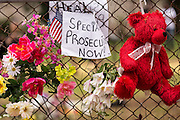 Flowers and notes decorate a fence as a prayer vigil is held by Rev. Al Sharpton on the spot where unarmed motorist Walter Scott was gunned down by police April 12, 2015 in North Charleston, South Carolina. About 100 people showed up for the brief vigil following a healing service at Charity Mission Baptist Church.