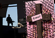 A soldier is silhouetted at the Juarez Avenue border crossing in the USA as by a memorial to women killed in violence in Juarez, Mexico January 14, 2009. An ongoing drug war has already claimed more than 40 people since the start of the year. More than 1600 people were killed in Juarez in 2008, making Juarez the most violent city in Mexico.    (Photo by Richard Ellis)