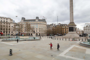 Two men walk across an almost deserted Trafalgar Square in London on March 20th, 2020. The centre of London is extremely quiet after the numbers of tourists has plummeted and locals limit their activities due to the Coronavirus crisis.