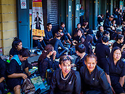 27 SEPTEMBER 2017 - BANGKOK, THAILAND: People on a sidewalk across the street from the Grand Palace after paying respects to the funeral urn of the late King. The Royal Household has announced that the palace will close to the public, including tourists, on 04 October 2017 to allow officials to complete preparations for the cremation of Bhumibol Adulyadej, the King of Thailand, who died on 13 October 2016. They also extended the official mourning period by 15 days. It was originally set to end on 13 October 2017 but now will end on 26 October 2017, the day of the King's cremation.    PHOTO BY JACK KURTZ