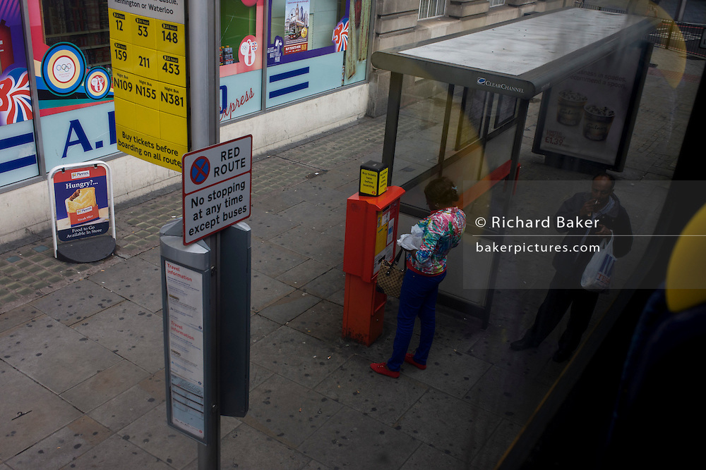 Female bus user inserts cash into London transport ticket machine in city street.