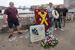 June 24, 2017 - London, UK - London, UK. 24th September 2017.  Supporters pose with wreaths on London Bridge after the march by well over a thousand supporters of the recently formed Football Lads Alliance marched to the centre of London Bridge to protest what they see as the UK government's reluctance in tackling the current extremism problem. They marched in silence and without banners, posters or placards to a short rally and moment of silence. Police had imposed conditions on the event under Section 12 and 14 of the Public Order Act, 1986, due to concerns of serious public disorder, and disruption to the community, which prevented them from marching to Borough Market.  Peter Marshall ImagesLive (Credit Image: © Peter Marshall/ImagesLive via ZUMA Wire)