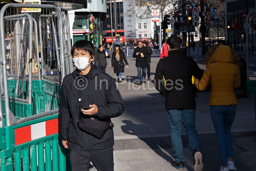Leicester Square almost deserted and people wearing face masks due to the Covid-19 outbreak social distancing on what would normally be a busy, bustling day with hoards of people out to shop and socialise on 22nd March 2020 in London, England, United Kingdom. Coronavirus or Covid-19 is a new respiratory illness that has not previously been seen in humans. While much or Europe has been placed into lockdown, the UK government has announced more stringent rules as part of their long term strategy, and in particular social distancing.