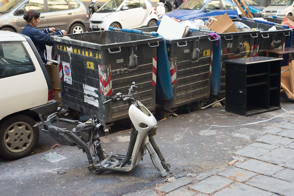 A motorbike sits stripped of all of its parts, while a woman prepares to throw things in a dumpster on the streets of Naples, Italy