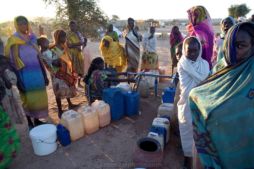The Breidjing Refugee Camp, Eastern Chad on the Sudanese border shelters 30,000 people who have fled their homes in Darfur, Sudan. Water is a constant preoccupation in the Breidjing Refugee Camp. Every day, lines of women and children carry jugs and pots of drinking and cooking water from distribution points to their tents. To get extra water to wash clothes, families dig pits in nearby wadis (seasonal river beds), creating shallow pools from which they scoop out water. In November, the camp wadi had water three feet below the surface. As the dry season advances, the sand pits get deeper and deeper. (Supporting image from the project Hungry Planet: What the World Eats.)