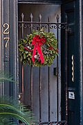 A Christmas wreath hangs from a historic home along State Street in Charleston, SC.