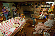 Farmer Joel Salatin (with cat in lap)  discusses business for the next day with one of his apprentices at his farm in Swoope, Virginia. (Joel Salatin is featured in the book What I Eat: Around the World in 80 Diets.)